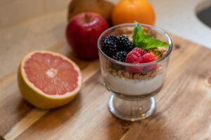 Fresh grapefruit half, whole apples and oranges served with a vanilla, granola, raspberry and blueberry parfait garnished with a mint leaf, presented on a wooden cutting board