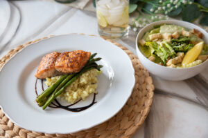 Plated dinner, seared salmon, creamy mashed potatoes, asparagus with a sauce reduction served with a Caesar salad, croutons, cheese and a lemon wedge, and a glass of ginger ale with ice on a dining table decorated with eucalyptus and small white flowers