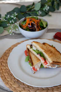 Lunch, a plated turkey, lettuce, tomato, arugula and mayo sandwich cut in half with a green side salad garnished with carrot shavings on a dining table decorated with eucalyptus and small white flowers