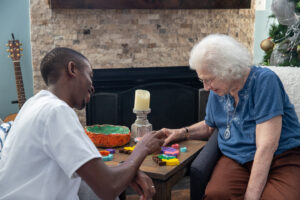 Elderly woman and caregiver do puzzles in front of fireplace