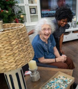 Elderly woman laughing with caregiver in living room