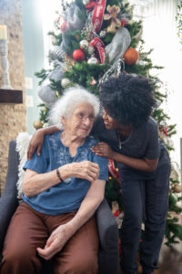 Elderly woman and caretaker embracing in front of Christmas tree