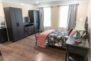 elderly care bedroom with bed, tv, and closets.